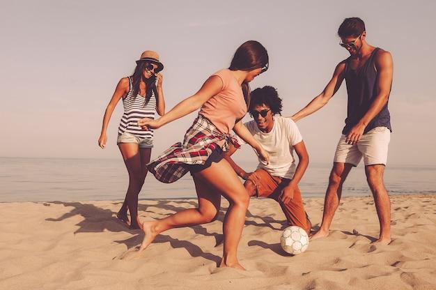 Zabawa z przyjaciółmi. grupa wesołych młodych ludzi bawiących się piłką nożną na plaży z morzem w tle
