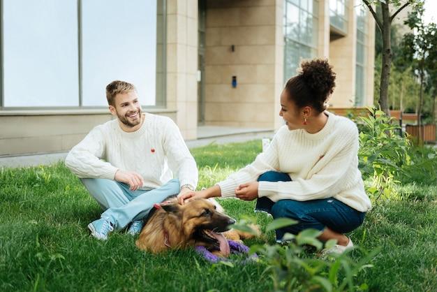 Zabawa z psem. urocza para ubrana w ładne, stylowe białe swetry z dzianiny bawi się ze swoim miłym psem