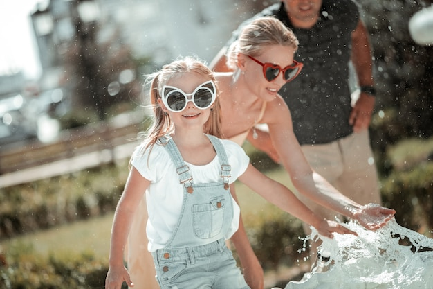 Zabawa z rodzicami. uśmiechnięta dziewczynka bawi się rozpryskami fontanny stojąc przed rodzicami w upalny letni dzień.