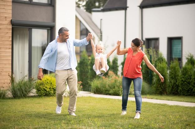 Zabawa z rodzicami. wesoła piękna córka czuje się szczęśliwa, bawiąc się z rodzicami w pobliżu domu