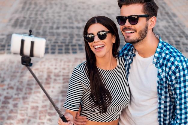 Zabawa z selfie. widok z góry na piękną, młodą, kochającą się parę, która robi selfie na smartfonie, stojąc na zewnątrz
