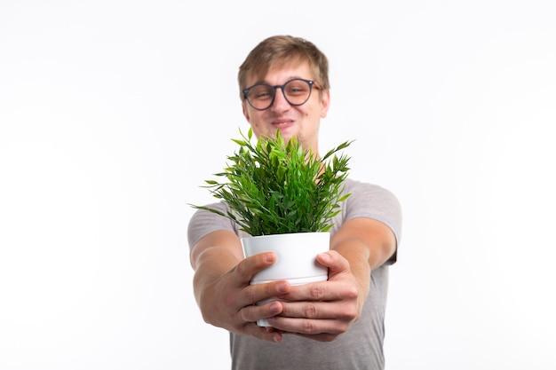 Zabawa, żart, nerd i maniakiem koncepcja - zabawny człowiek trzymający kwiat w doniczce na białej powierzchni.
