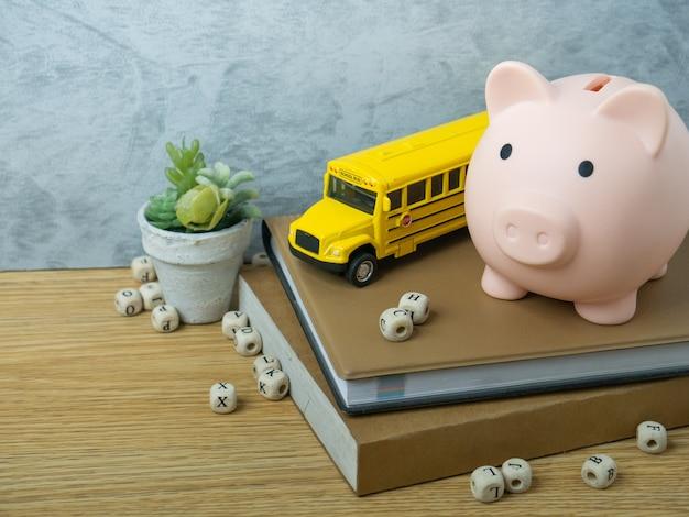 Zabawka autobus szkolny i skarbonka na drewnianym stole na powrót do koncepcji szkoły lub edukacji