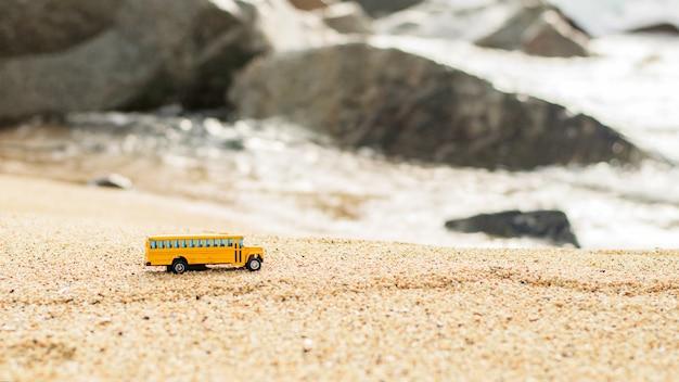 Zabawka autobusu szkolnego na piasku w pobliżu kamieni