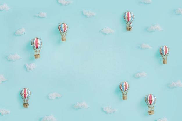 Zabawka balonów na ogrzane powietrze i chmury na niebieskiej ścianie z miejsca na kopię