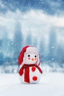 Zabawka bałwana na tle zimowego krajobrazu podczas opadów śniegu. kartka noworoczna i świąteczna