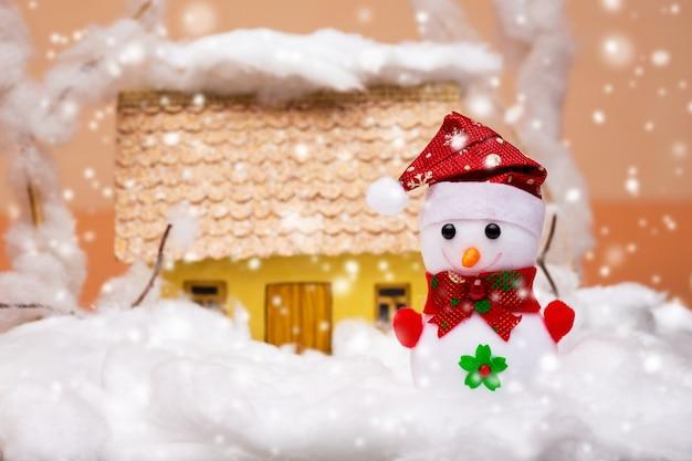 Zabawka bałwana w śniegu w pobliżu domu podczas opadów śniegu