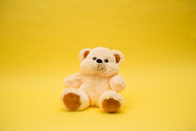 Zabawka beżowy miś na żółtym tle na białym tle z kopią miejsca