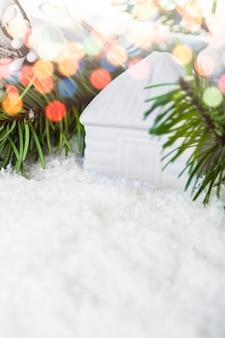 Zabawka biały dom w śniegu i jodły. pocztówka świąteczna z miejscem na sopy na pozdrowienia