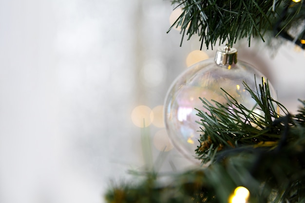 Zabawka choinkowa, przezroczysta szklana kula na gałęzi z bokeh świateł girlandami