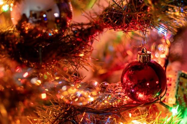 Zabawka choinkowa w postaci czerwonej bombki wisi na świerkowej gałęzi w otoczeniu noworocznych dekoracji