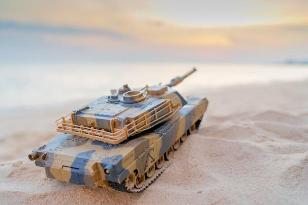 Zabawka czołg na piasku na plaży w pobliżu, brązowa zabawka czołgu navy