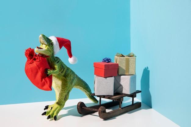Zabawka dinozaura z czerwonym workiem i saniami