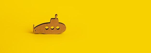 Zabawka drewniana łódź podwodna na żółtym tle, makieta panoramiczna