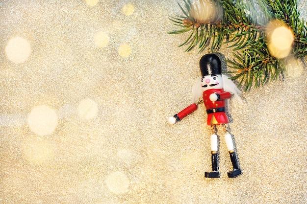Zabawka dziadek do orzechów na świerkowej gałęzi na białym drewnianym tle ze światłami