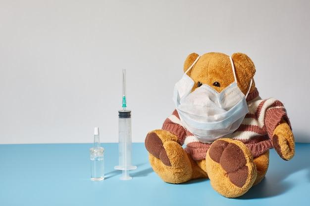 Zabawka dziecięca niedźwiedź w medycznej białej masce na niebiesko