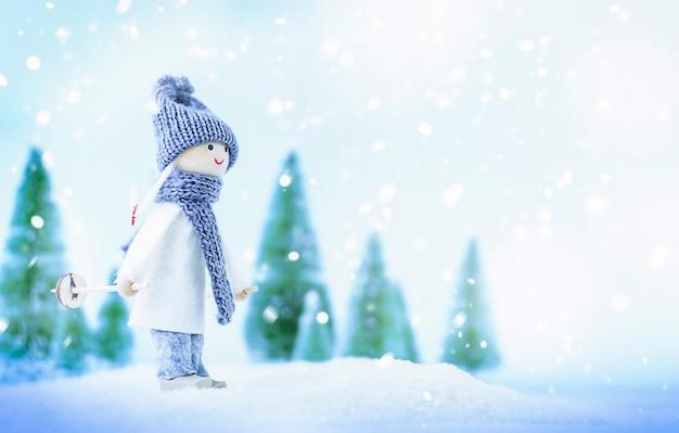 Zabawka dziewczyna na nartach w zimowym lesie