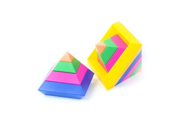 Zabawka edukacyjna dla dzieci rozwijająca zdolności motoryczne, wielokolorowe piramidy, na białym tle.