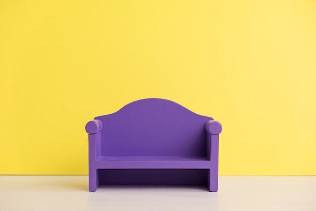 Zabawka fioletowa sofa na żółtej ścianie. miniaturowe drewniane meble zabawkowe dla dzieci, jak nauczyć się ozdabiać tam salon. komfort w domu.