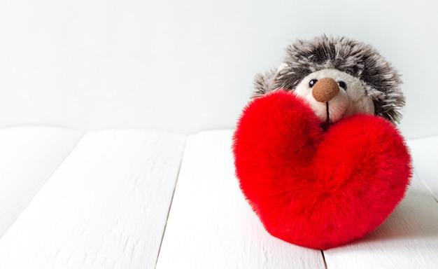 Zabawka jeż i czerwone miękkie serce na białym tle drewniane na walentynki z miejsca na kopię