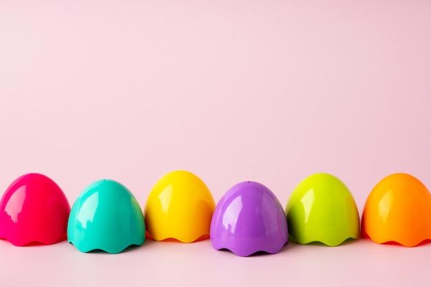 Zabawka kolorowe plastikowe jajka na różowym tle. zabawka jasne tło wielkanoc. koncepcja wielkanocy montessori. pisanki dla dzieci.