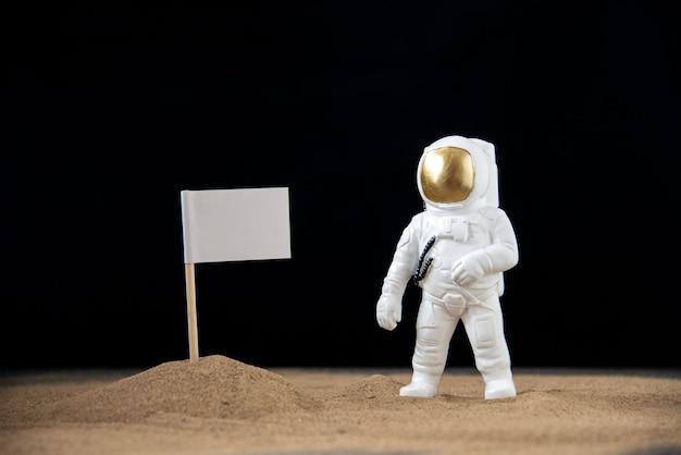 Zabawka kosmonauta na księżycu z flagą na ciemnej powierzchni