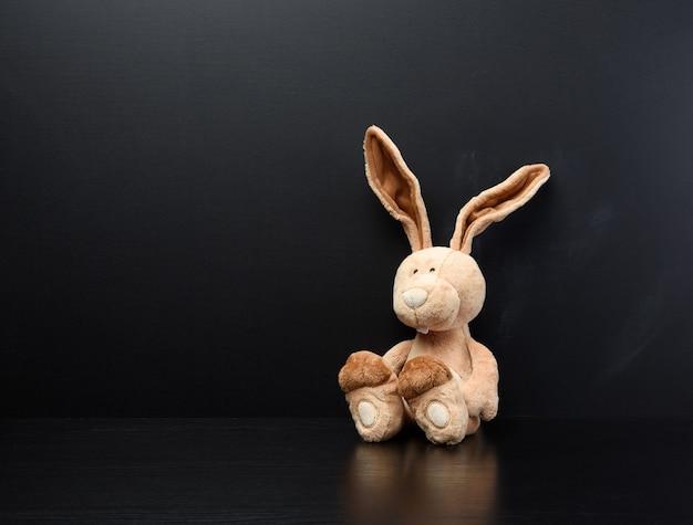 Zabawka króliczek na czarnej kredowej tablicy szkolnej, miejsce do pisania