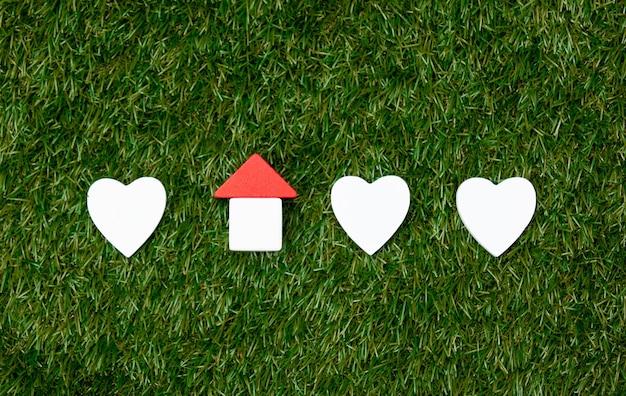 Zabawka kształty domu i serca na zielonej trawie.