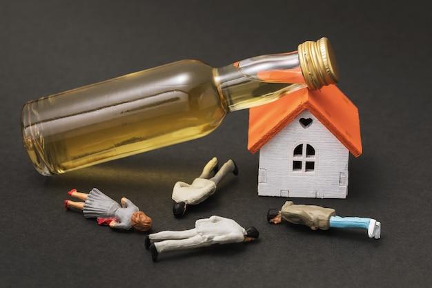 Zabawka mężczyźni z tworzywa sztucznego mały dom i butelka whisky koncepcja na temat nadużywania alkoholu
