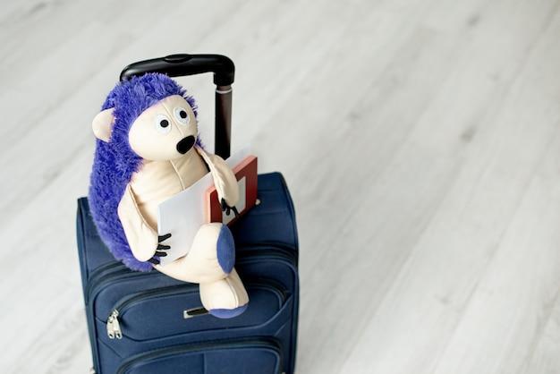 Zabawka na walizce z liśćmi palmowymi, roślina domowa. jeż turystyczny. zapakowana walizka stoi w domu.
