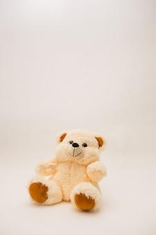 Zabawka niedźwiedź beżowy orientacji pionowej na białej ścianie na białym tle z kopią miejsca
