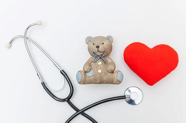 Zabawka niedźwiedź czerwone serce i medycyna sprzęt stetoskop na białym tle