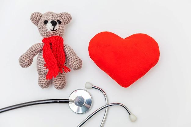 Zabawka niedźwiedź czerwone serce i stetoskop na białym tle