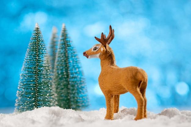Zabawka ozdoba jelenia z choinkami i śniegiem