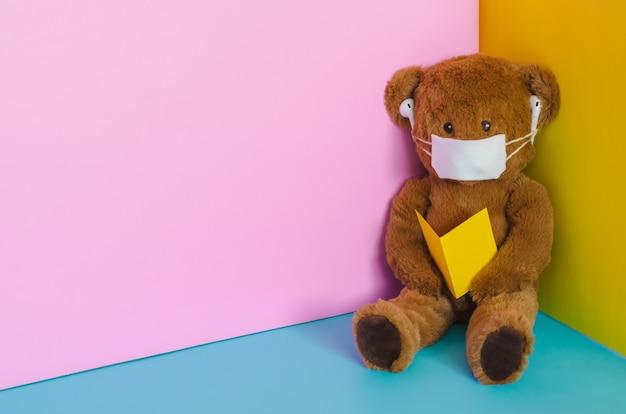 Zabawka pluszowego misia, noszenie maski, słuchanie piosenki i czytanie czegoś na rogu. trzymaj się z dala od koncepcji wirusa.