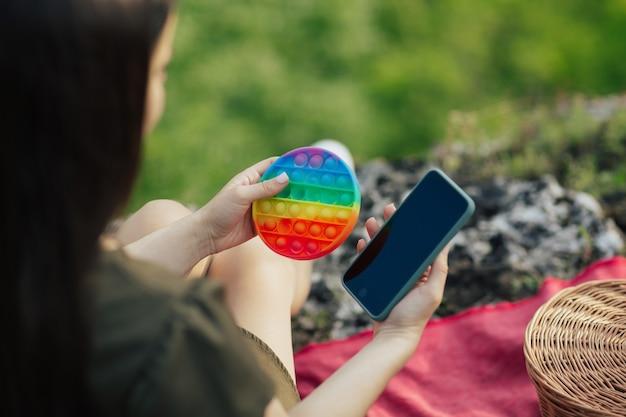 Zabawka pop to i telefon w rękach dziewczyny