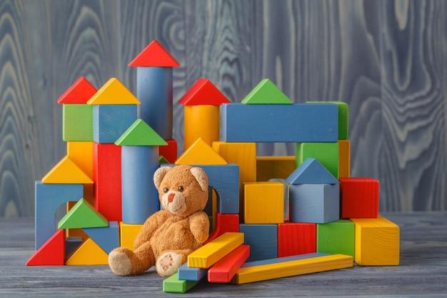 Zabawka retro niedźwiedź sam na drewnianej podłodze z bloków budownictwa