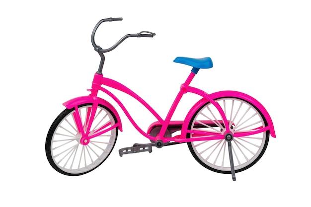 Zabawka różowy rower z niebieskim siedzeniem na białym tle na białej powierzchni