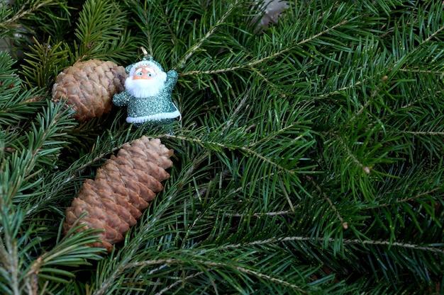 Zabawka świętego mikołaja przeciwko gałęziom zjadł stożek