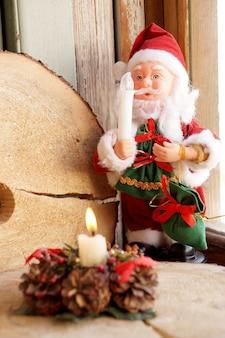 Zabawka święty mikołaj w czerwonym ubraniu ze świecą w dłoni