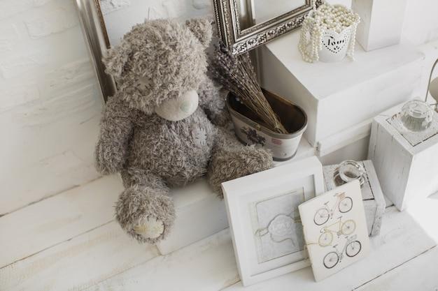 Zabawka szary niedźwiedź w białym studiu fotograficznym. obrazy, koraliki, ramki, rower.