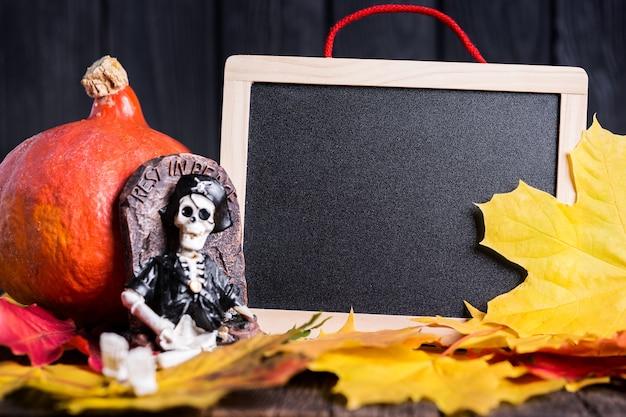 Zabawka szkielet i tablica na liściach klonu na drewnianym tle