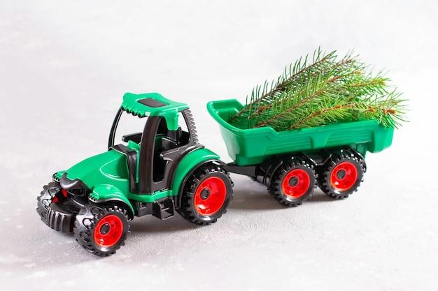 Zabawka traktor przewożąca gałąź choinki. dzieci, święta, boże narodzenie, nowy rok