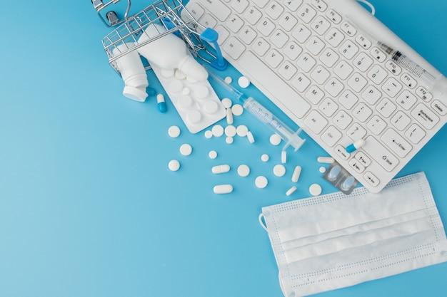 Zabawka wózek na zakupy z lekarstwami i klawiaturą. tabletki, blistry, butelki medyczne, termometr, maska ochronna na niebieskim tle. widok z góry z miejscem na tekst