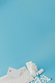 Zabawka wózek na zakupy z lekarstwami i klawiaturą. tabletki, blistry, butelki medyczne, termometr, maska ochronna na niebieskim tle