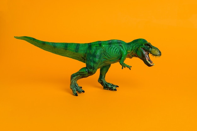 Zabawka z zielonego dinozaura z otwartymi ustami na żywej pomarańczy