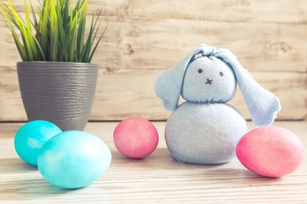 Zabawka zajączek i pisanki na drewnianym stole. ozdoby wielkanocne, symbol wakacji.