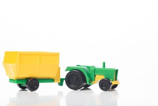 Zabawka zielony ciągnik żółty przyczepa na białym tle. element projektu.
