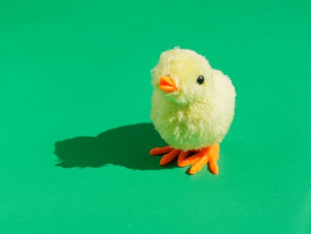 Zabawka żółty kurczak na zielonym tle.