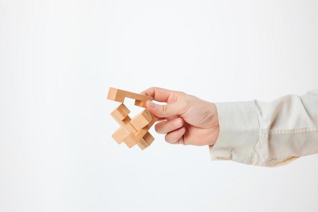 Zabawkarska drewniana łamigłówka w ręce odizolowywającej na biel ścianie